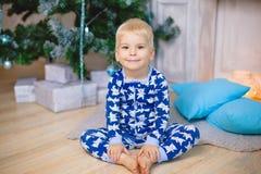 睡衣的小男孩有熊的坐地板并且微笑 握他的腿 免版税图库摄影