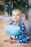 睡衣的小男孩有熊的微笑,坐并且拥抱蓝色枕头 免版税库存图片