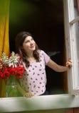 睡衣的少年女孩叫醒与花束的开窗口 免版税图库摄影