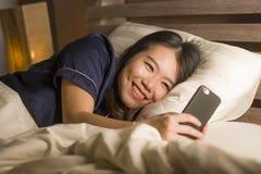 睡衣的年轻美丽和愉快的亚裔日本妇女使用发短信与她男朋友或享用的手机社会媒介 库存照片