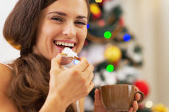 睡衣的愉快的少妇饮用快餐在圣诞树附近 图库摄影