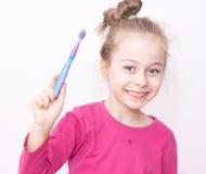 睡衣的愉快的微笑的儿童女孩与牙刷-上床时间 库存照片