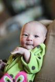睡衣的新出生的女婴在父亲的膝盖 免版税库存图片