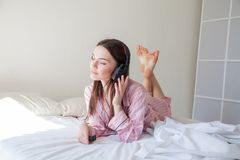 睡衣的深色的妇女听到音乐的在床上在 免版税库存图片