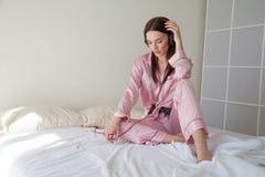 睡衣的深色的妇女听到音乐的在床上在 免版税图库摄影