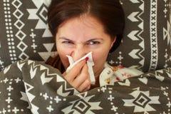 睡衣的病的少妇,放置在床上,被盖在鸭绒垫子下, 免版税库存照片