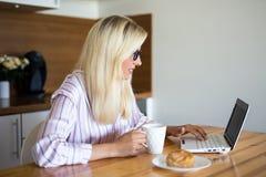 睡衣的白肤金发的妇女喝咖啡和使用膝上型计算机的在k 免版税库存图片