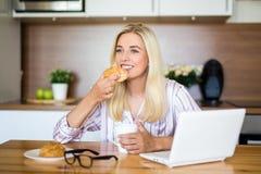 睡衣的白肤金发的妇女喝咖啡和吃在t的甜小圆面包 库存照片