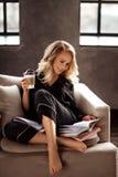 睡衣的美丽的快乐的年轻白肤金发的女性享用早晨咖啡,读书为介绍做准备,坐o 免版税库存照片