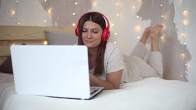睡衣的美丽的性感的女孩听到在耳机的音乐的使用充满说谎在床上的好心情的膝上型计算机 影视素材