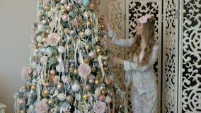 睡衣的美丽的白肤金发的女孩装饰圣诞树的 股票视频