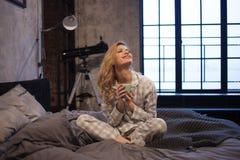 睡衣的迷人的年轻女人,坐在床和饮用的早晨咖啡上 图库摄影