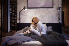 睡衣的迷人的年轻女人,坐在床和饮用的早晨咖啡上 免版税库存照片