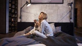 睡衣的迷人的年轻女人,坐在床和饮用的早晨咖啡上 免版税库存图片