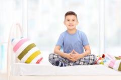 睡衣的逗人喜爱的小男孩坐床 免版税库存图片