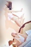 睡衣的他们中的一个2名性感的美丽的愉快的妇女跳跃,当看她的其他在床上时 免版税库存图片