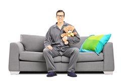 睡衣的年轻人坐有玩具熊的沙发 免版税库存照片