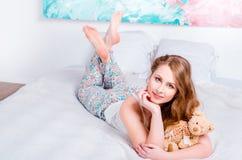 睡衣的年轻人相当白肤金发的女孩在床上在他的屋子和举行里一个软的玩具在手和微笑上 图库摄影