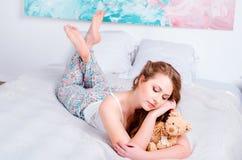 睡衣的年轻人相当白肤金发的女孩在床上在他的屋子和举行里一个软的玩具在手和微笑上 免版税库存图片