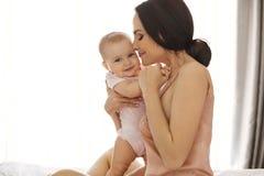 睡衣裤微笑的拥抱的年轻可爱的妈妈亲吻她的坐在窗口的床上的婴孩 闭合的眼睛 免版税图库摄影