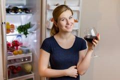睡衣裤的少妇喝红葡萄酒的在冰箱附近 库存照片