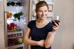 睡衣裤的少妇喝红葡萄酒的在冰箱附近 库存图片