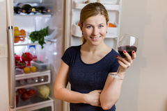 睡衣裤的少妇喝红葡萄酒的在冰箱附近 图库摄影