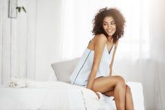 睡衣裤的梦想的嫩非洲女孩坐在早晨微笑的认为的床 复制空间 免版税库存图片