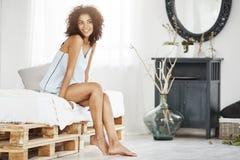 睡衣裤的梦想的嫩非洲女孩坐在早晨微笑的认为的床 免版税库存照片