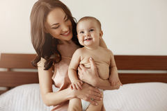 睡衣裤的年轻美丽的愉快的母亲和她新出生的婴孩坐在早晨微笑的一起使用的床 图库摄影
