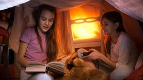 睡衣阅读书的两个逗人喜爱的姐妹在帐篷在家由毯子制成 免版税库存照片