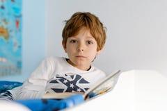 睡衣阅读书的逗人喜爱的白肤金发的小孩男孩在他的卧室 免版税库存照片
