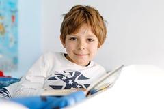睡衣阅读书的逗人喜爱的白肤金发的小孩男孩在他的卧室 库存照片