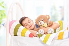 睡觉与一个玩具熊的可爱的男孩在床上 图库摄影