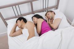 睡觉与两个人的少妇在床上 免版税库存图片