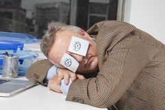 睡觉与关于眼睛的稠粘的笔记的商人在书桌在办公室 免版税库存图片