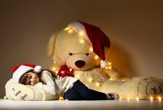 睡觉与在圣诞节圣诞老人红色帽子的大软的玩具熊玩具的女孩 库存照片