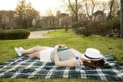 睡觉与在她的面孔的一个帽子的妇女在公园 图库摄影
