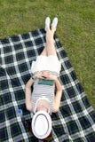 睡觉与在她的面孔的一个帽子的妇女在公园 免版税库存照片