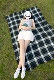 睡觉与在她的面孔的一个帽子的妇女在公园 免版税库存图片