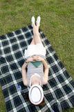 睡觉与在她的面孔的一个帽子的妇女在公园 库存图片