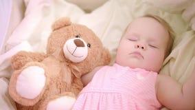 睡觉与在小儿床的玩具的女婴 甜上床时间 小女孩梦想在床上 影视素材