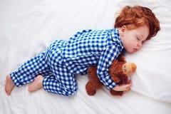 睡觉与在法绒睡衣的长毛绒玩具的可爱的红头发人小孩婴孩 免版税库存照片