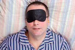 睡觉与在眼睛的一个面具的人 免版税库存照片