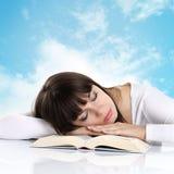 睡觉与在背景天空的一本书的女孩与云彩 免版税库存照片