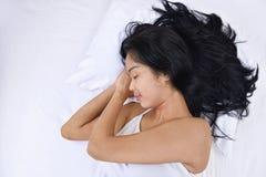 睡觉与头的年轻亚裔妇女在手边说谎 库存图片