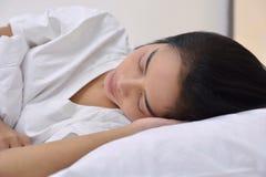 睡觉与头的年轻亚裔妇女在手边说谎 库存照片