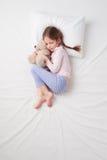 睡觉与女用连杉衬裤的小逗人喜爱的女孩顶视图  免版税图库摄影