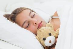 睡觉与她的玩具熊的快乐的女孩 免版税库存照片