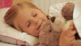睡觉与她的玩具熊的逗人喜爱的小女孩 股票视频